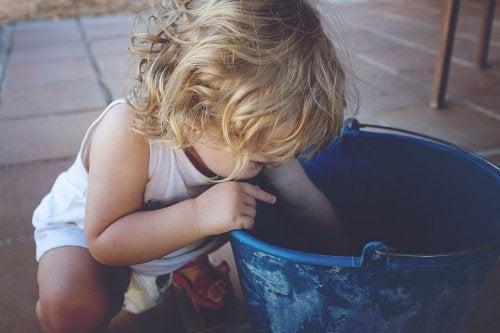enfant gaucher regardant dans un seau