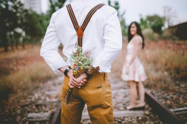 homme offrant des fleurs