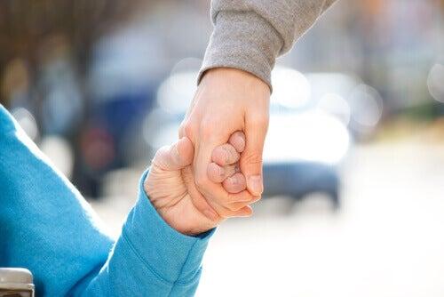 personne handicapée tenant la main d'une autre personne