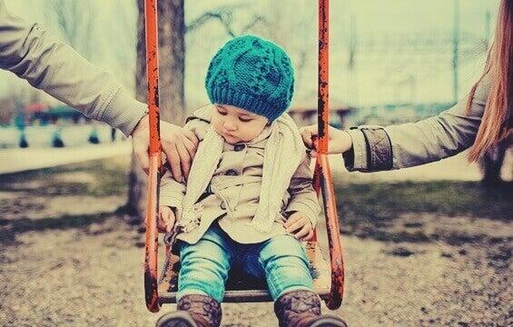 enfant sur une balançoire avec les bras de ses parents sur les côtés