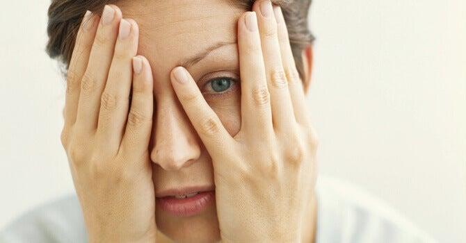 femme qui se cache le visage avec les deux mains