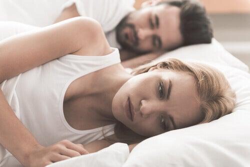 femme réveillée et pertrubée par les problèmes sexuels avec son conjoint