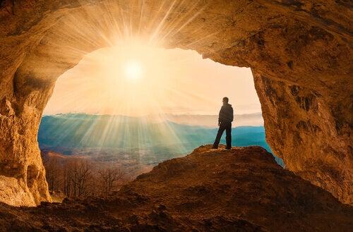homme dans une grotte face au soleil