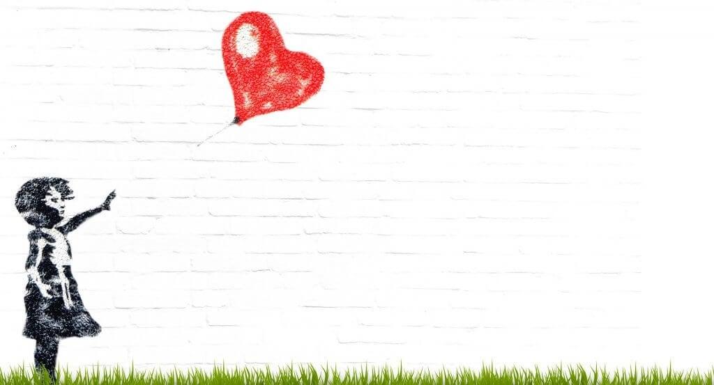 petite fille lâchant un coeur en forme de ballon