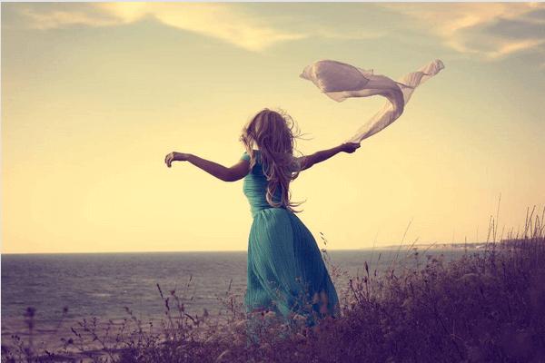 femme au bord de la mer laissant s'envoler un voile