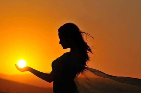 femme tenant le soleil dans ses mains
