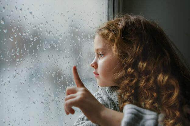 petite fille pensive regardant la pluie par la fenêtre