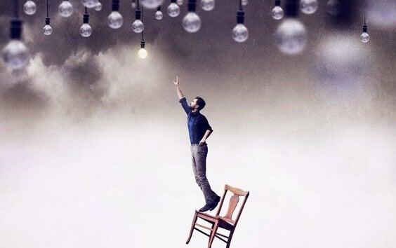 homme tentant d'attraper une ampoule allumée, ce qui représente une idée