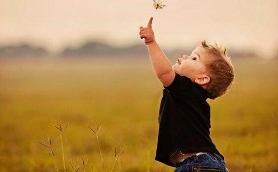 enfant essayant d'attraper un papillon