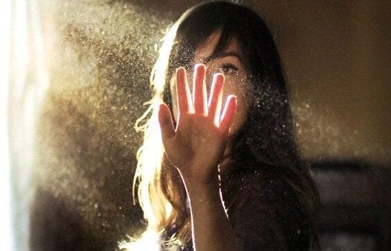 femme mettant sa main dans un rayon de soleil