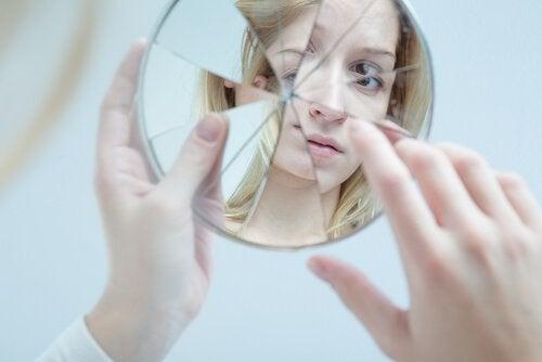 femme se regardant dans un miroir cassé
