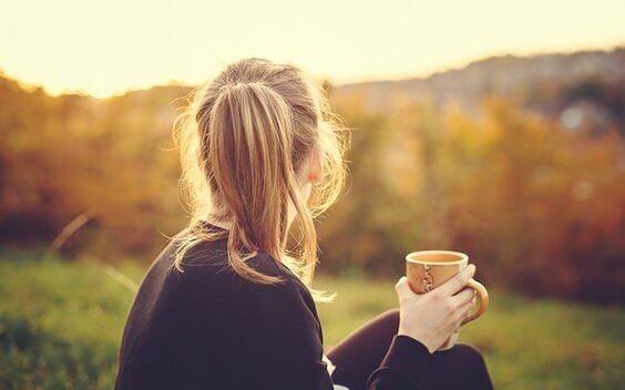 femme dans un champ avec une tasse