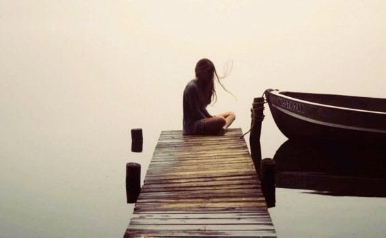 femme assise au bout d'un ponton