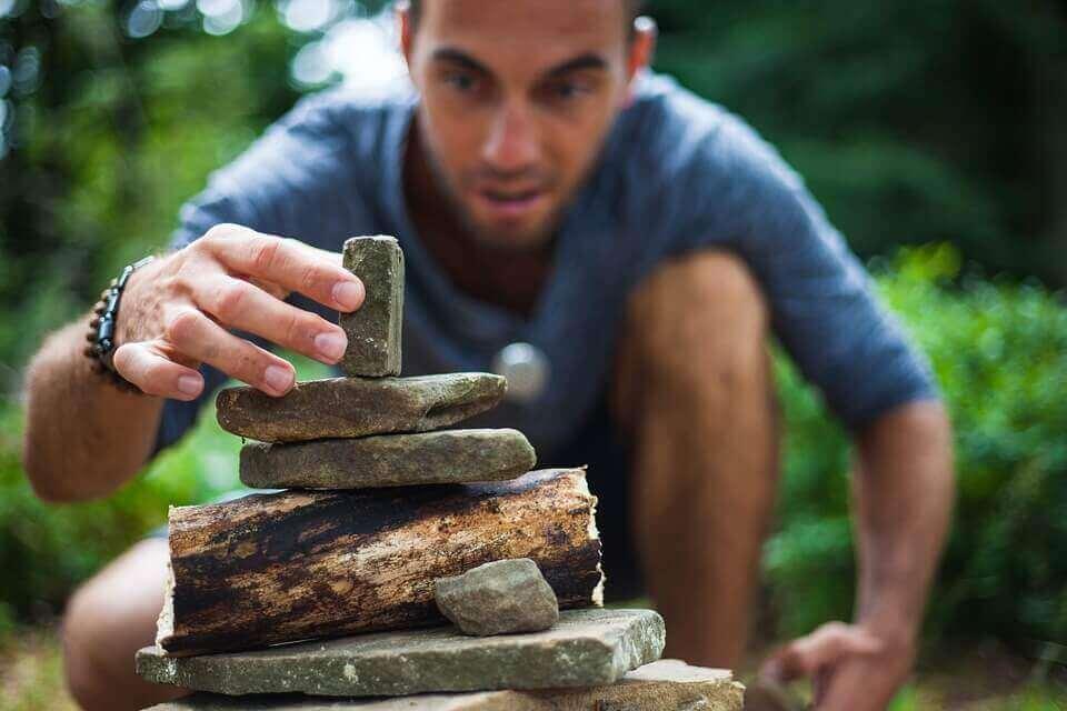 homme superposant des pierres