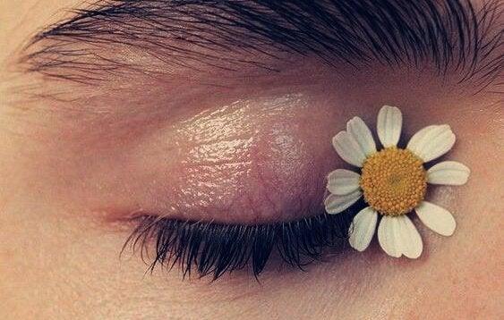 femme avec une fleur sur l'oeil
