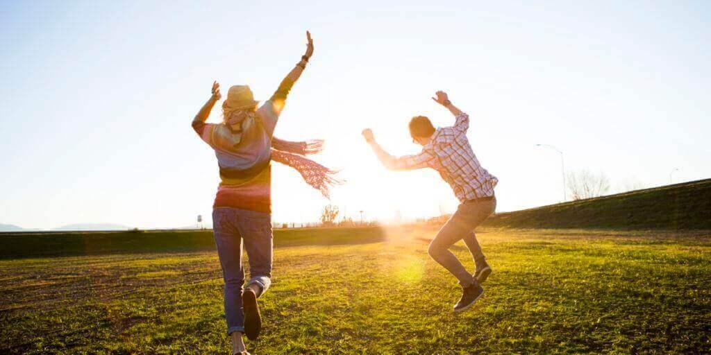 couple sautant dans le champ
