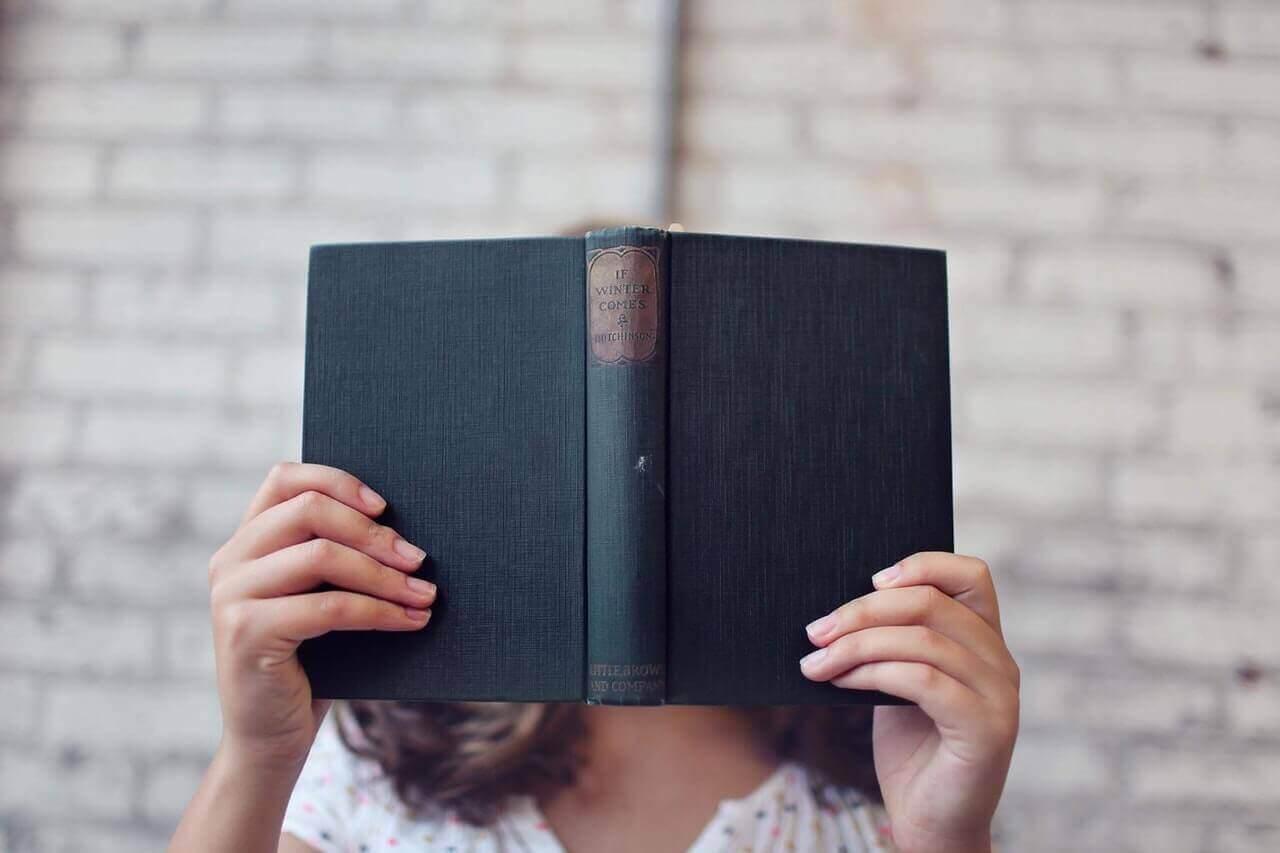 Femme avec un livre devant le visage