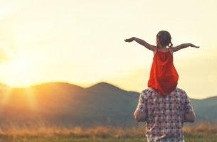 Père et fille sur les épaules en regardant le soleil