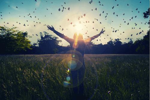 femme entourée d'oiseaux dans la nature