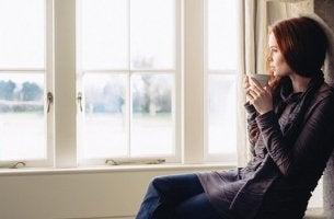 femme qui regarde par la fenêtre