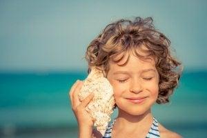 enfant qui écoute dans un coquillage