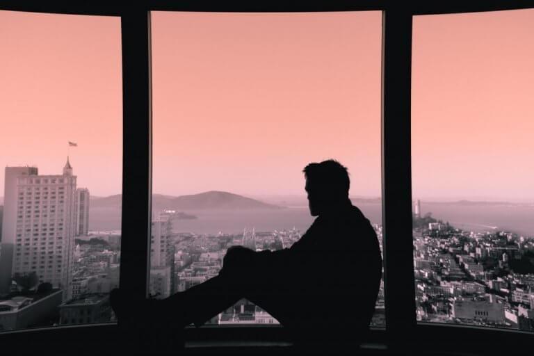 homme regardant par la fenêtre