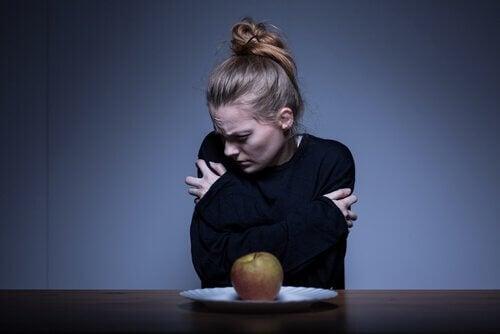 femme anorexique face a une pomme