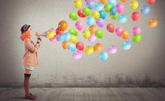 femme clown avec mégaphone d'où sortent des ballons