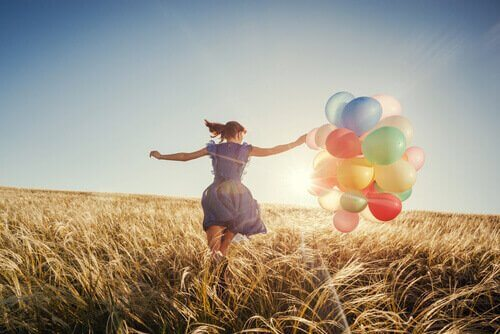 femme courant dans un champ avec des ballons