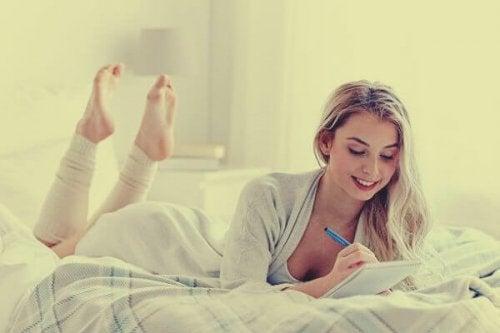 femme écrivant dans son journal de cinq minutes
