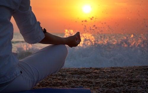 femme faisant de la méditation au bord de la mer pour augmenter son taux de sérotonine