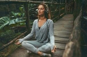 Femme en position du lotus en train d'écouter de la musique