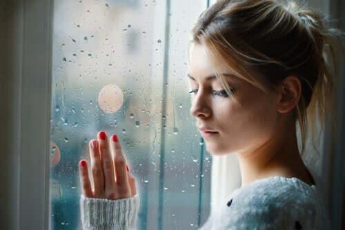 femme triste à la fenêtre devant apprendre à lâcher prise