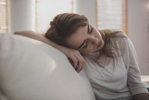 Une femme qui dort contre son canapé