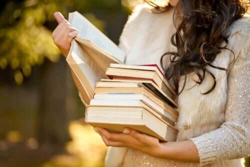 Une femme porte une pile de livres