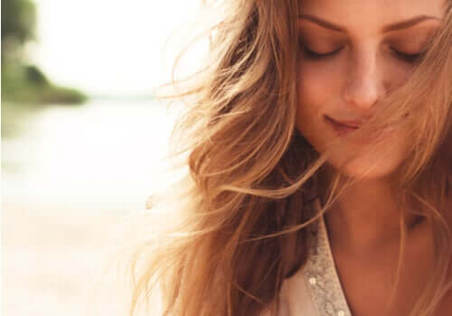 une femme souriante qui regarde vers le bas