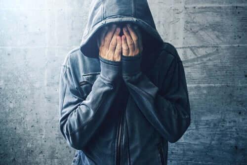 Un homme se cache le visage avec les mains