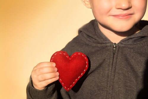 Un petit garçon qui tient un coeur avec sa main