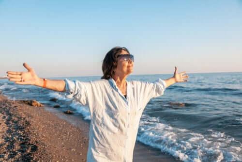 Une femme appartenant au quatrième âge les bras ouverts face à la mer