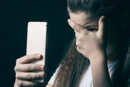 Une jeune fille qui se cache le visage en tenant son portable