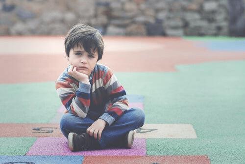 Un enfant est assis dans une cour de récréation