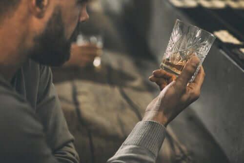 Un homme regardant un verre d'alcool