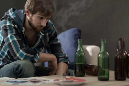 Un jeune homme face à une table contenant des bouteilles d'alcool