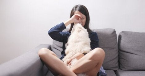 Une femme pleurant avec son chien sur son canapé