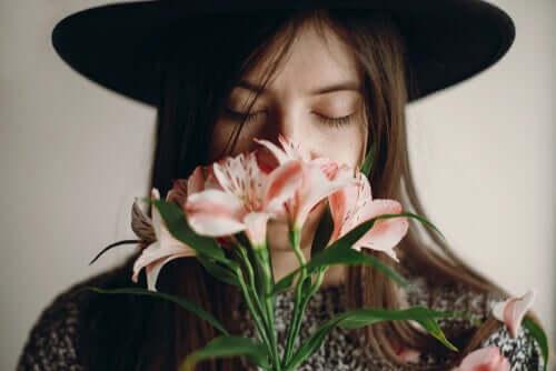 Une femme sentant des fleurs grâce à son bulbe olfactif