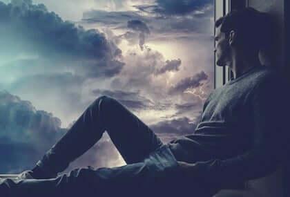 Un homme face à une fenêtre et un nuage