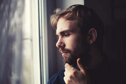 Un homme qui regarde par la fenêtre dans le noir
