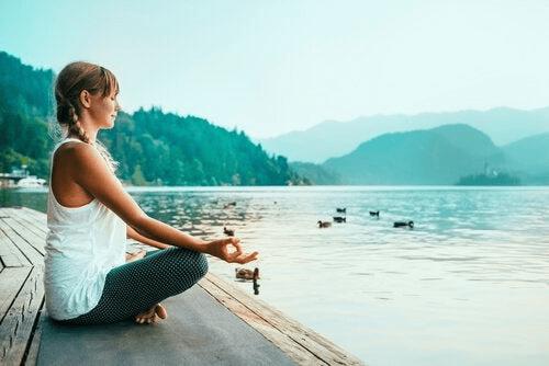 Une femme qui s'adonne au mindfulness au bord d'un lac