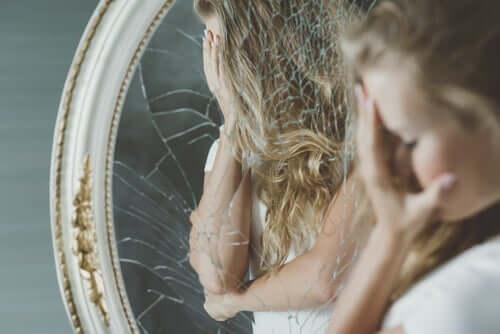 Une femme face à un miroir cassé