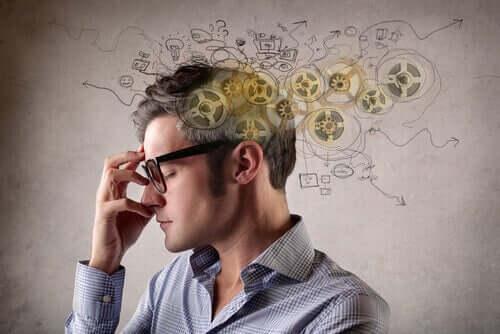 Un homme à lunettes qui pense au biais de négativité